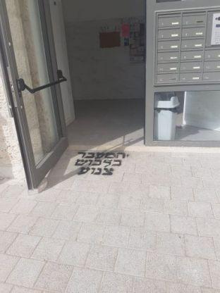 כתובות גרפיטי בנוסח המעבר בלבוש צנוע בכניסה לבנייני מגורים