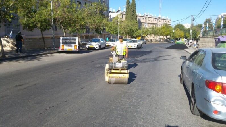 עובד אגף שפע מהדק עם מכבש את  'הפלסטר' לכביש